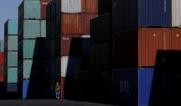 FILE PHOTO: A worker walks in a container area at a port in Tokyo, Japan January 25, 2016. REUTERS/Toru Hanai/File Photo