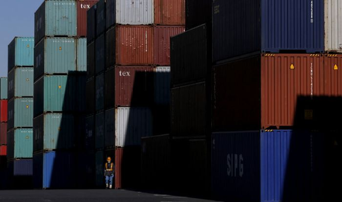 FILE PHOTO: Worker walks in a container area at a port in Tokyo
