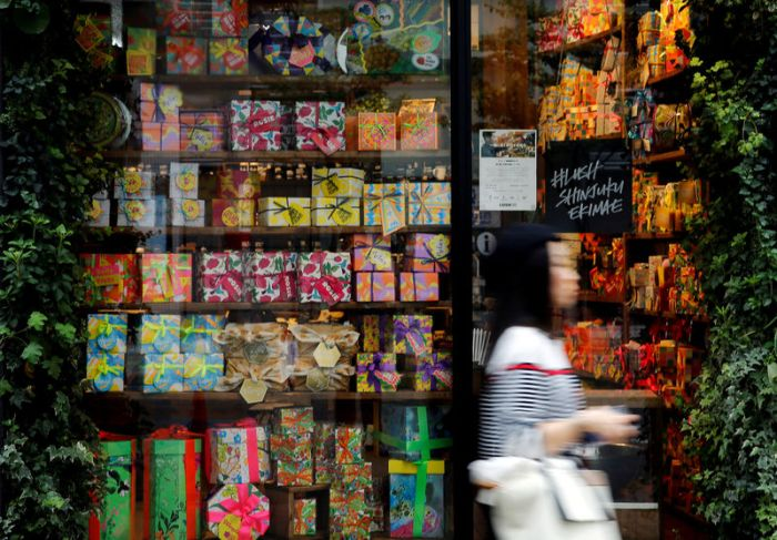 Woman walks outside a shop in a shopping district in Tokyo