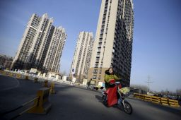 A woman rides past a residential compound in Beijing's Tongzhou district