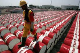 File photo of an employee of Indonesian oil company Pertamina walking on the top of drums at Jakarta's oil storage depot.