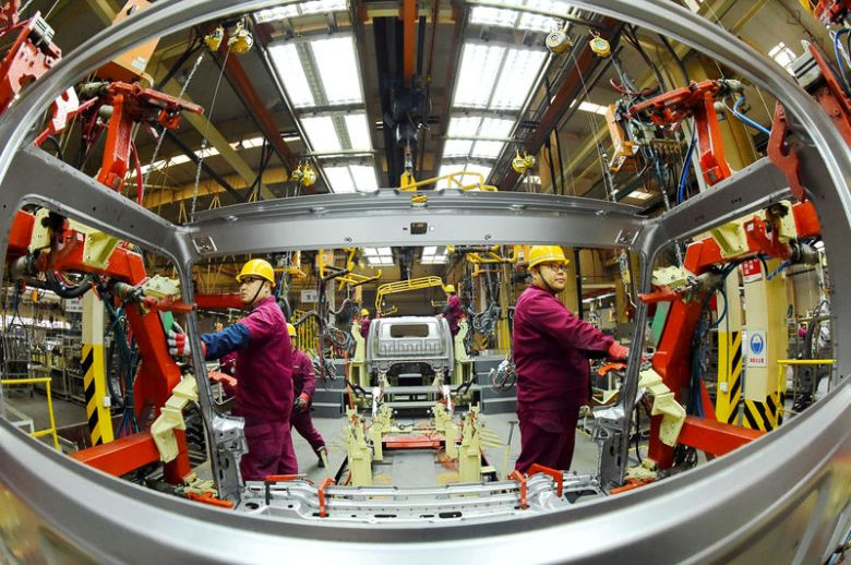 FILE PHOTO: Employees work on a production line manufacturing light trucks at a JAC Motors plant in Weifang