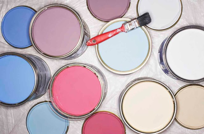 Paintbrush balancing on open tins of paint, overhead view, close-up